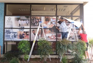 Staff from All Pro Displays and Graphics and LiveWire Creative Services install new photo decals for the Health Professions Center window panels at the corner of Palomares Street and the Esplanade for the College of Pharmacy. (Jeff Malet, WesternU)