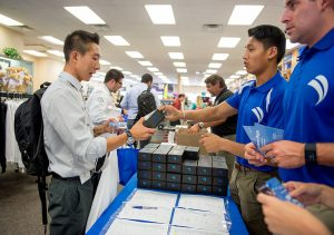 First-year COMP student Jin Lee, left, receives his new SonoSim ultrasound training probe and software from SonoSim intern Matt Marcelino Wednesday, August 3, 2016 at the WesternU Bookstore during Welcome Week. (Jeff Malet, WesternU)