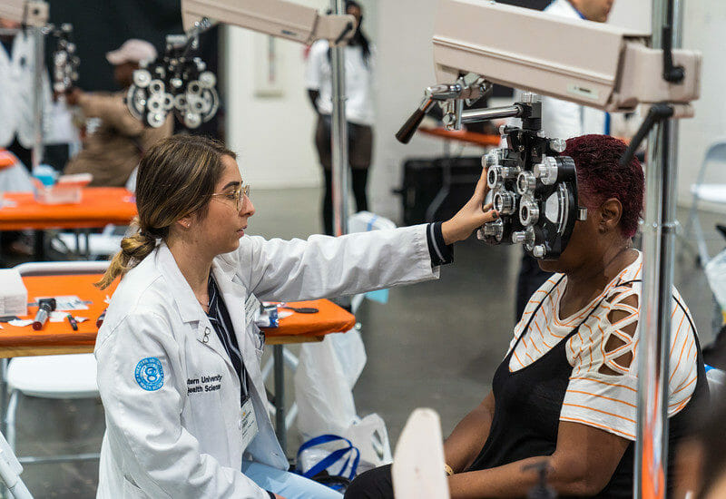 WesternU College of Optometry students, faculty and staff took part in a free mega-clicnic, Care Harbor LA Friday, Nov. 15, 2019. Students and faculty from other colleges plan to participate over the weekend. Patient Deberal Cooley gets a vision screening from third-year student optometrist Yeraz Kocharian.r(Jeff Malet, WesternU)