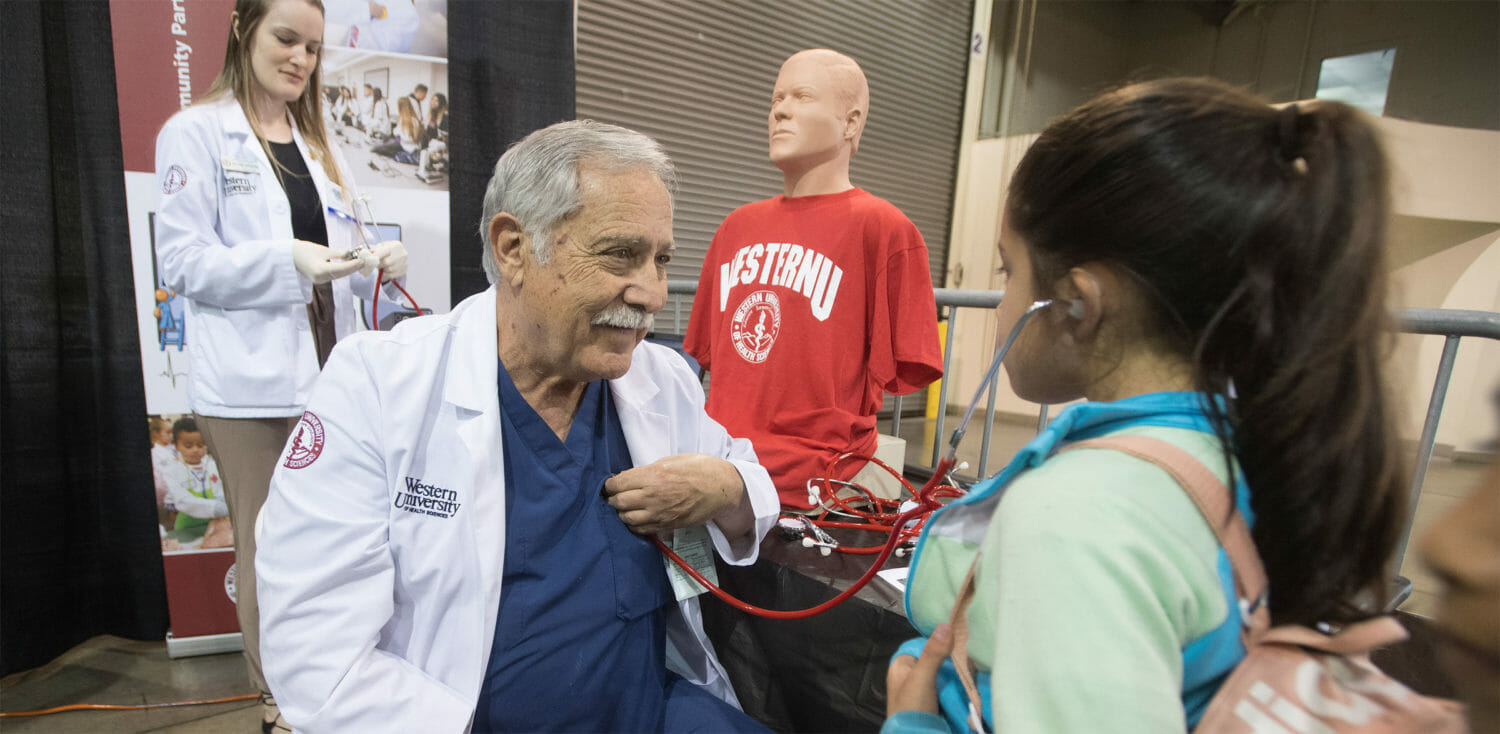 Young student uses a stethoscope to listen to heartbeat of a physician assistant teacher