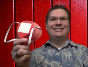 WesternU College of Optometry Associate Professor Joshua Cameron holds a red 3D printed mask in his right hand.